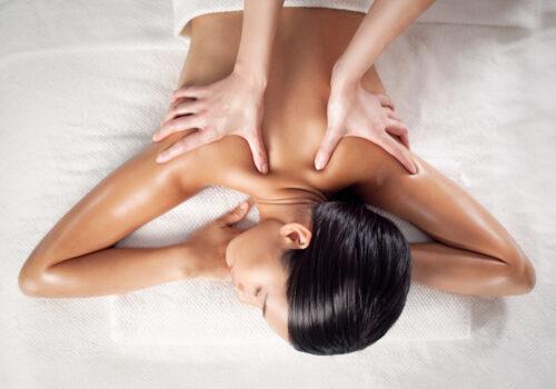 Asian,Woman,Enjoying,A,Back,Massage,At,A,Spa,Centre.